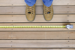 home exteriors contractor work boots standing on deck above yellow tape measure